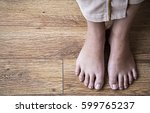 female feet on wooden background | Shutterstock . vector #599765237