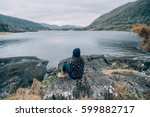woman sitting near the lake in... | Shutterstock . vector #599882717