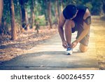 handsome man runners lace his... | Shutterstock . vector #600264557