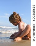 girl playing with sand on beach | Shutterstock . vector #600365693