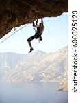 young man struggling to climb... | Shutterstock . vector #600395123