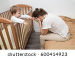 tired woman sitting on the bed ... | Shutterstock . vector #600414923