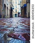 Small photo of Dark paving stones in a narrow alleyway
