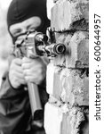 Small photo of Black & white photo of terrorist attack with automatic assault rifle in ruined building.Armed and dangerous military man in heavy combat ammunition targeting with machine gun in ruins.Airsoft training