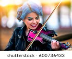 Small photo of Woman perform music on violin in park outdoor. Girl with blue hairstyle performing jazz on city street . Spring outside blur background.