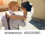 groom carries his bride in his... | Shutterstock . vector #601310387