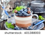 Small photo of Delicious three layered chocolate mousse dessert, de?orated with fresh blueberry, mint and candies, served in glass cup
