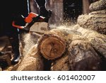 Small photo of Chainsaw in action cutting wood. Man cutting wood with saw, dust and movements.
