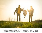 Small photo of Happy parents playing with their daughter in the park. Space for copy.