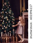 Small photo of Sisters in front of the fir-tree and fireplace with candles and gifts. New year's eve. Christmas eve. Cozy holiday at the fir-tree with lights and gold decor.