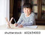 boy studying or doing home work | Shutterstock . vector #602654003