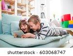 happy siblings lying on sofa at ...   Shutterstock . vector #603068747