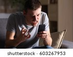 Small photo of Single angry person with a mobile phone sitting on a sofa in the living room in a house indoor with a dark background