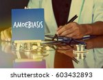 Small photo of Blue board easel written AMOEBIASIS and a stethoscope, the doctor on duty behind. Medicine and Healthcare Concept