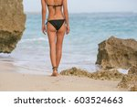 woman walking on sandy beach | Shutterstock . vector #603524663