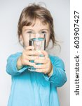 the child holds a glass of... | Shutterstock . vector #603907427