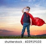 a boy stands on the grass in a... | Shutterstock . vector #603919103