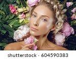 beautiful girl lying in flowers | Shutterstock . vector #604590383