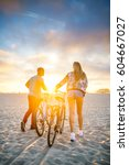 couple walking bikes together... | Shutterstock . vector #604667027