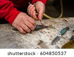 fishmonger cutting a small fish