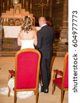 Small photo of Bride and groom at church wedding alter ceremony on the chairs