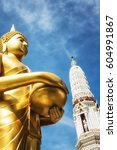 Small photo of The sculpture of Golden Buddha is standing with both hands holding an alms bowl.