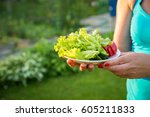 woman holding a plate with... | Shutterstock . vector #605211833