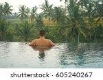 man in infinity pool in ubud ... | Shutterstock . vector #605240267