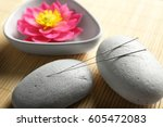 Small photo of Acupuncture needles with stones on bamboo mat