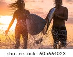 couple of surfers running with... | Shutterstock . vector #605664023