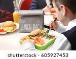 school boy eating delicious...   Shutterstock . vector #605927453
