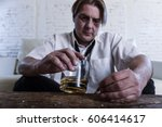 Small photo of sad depressed alcoholic businessman on his 40s with loose necktie looking wasted and drunk drinking whiskey and smoking at home living room couch in alcoholism problem and alcohol addiction