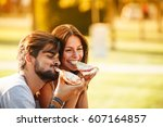 young couple sitting on park... | Shutterstock . vector #607164857