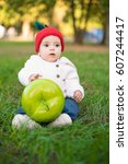 a cute baby girl in an apple... | Shutterstock . vector #607244417
