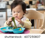 baby eating vegetable at home | Shutterstock . vector #607250837