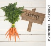 Small photo of Freshly Pulled Carrot Bunch with Green Tops on Distressed White Board Background, with a Rustic Brown Wood Sign Painted with Letters spelling the word Carrots. It's a square crop and is ready to use