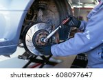 man fixing brake disk.... | Shutterstock . vector #608097647