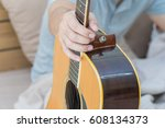 young man holding a guitar on... | Shutterstock . vector #608134373