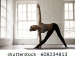 Small photo of Young attractive yogi woman practicing yoga concept, standing in Utthita Trikonasana exercise, extended triangle pose, working out, wearing sportswear, full length, white studio background, horizontal