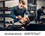 Small photo of Stylish barber shaving wiz sharp razor man's beard in a saloon.