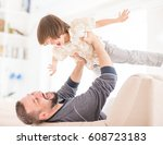Child Flying In Father Arms On...