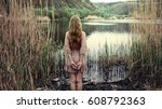lonely girl standing in reeds... | Shutterstock . vector #608792363