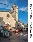 Small photo of Gréoux-les-Bains, France - July 08, 2016. Church and stone street with stalls at sunset in lovely village of Gréoux-les-Bains. Alpes-de-Haute-Provence department, Provence region, southeastern France