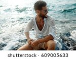 smiling guy in the sea spray on ... | Shutterstock . vector #609005633