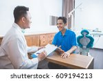 portrait of dentist talking to... | Shutterstock . vector #609194213