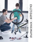 Small photo of father and son affixing bicycle wheel together on white