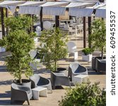 Small photo of Alfresco cafe with armchairs and tables on the summer garden terrace