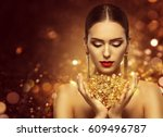 Fashion Model Holding Gold...