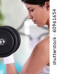 young woman lifting dumbbells | Shutterstock . vector #60961654