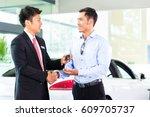 asian car salesman selling auto ... | Shutterstock . vector #609705737